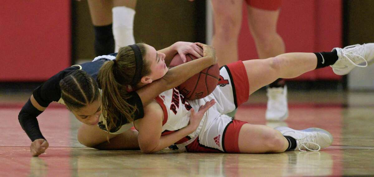 Notre Dame-Fairfield's Yamani McCollough (1) and Pomperaug's Madison Villa (35) wrestle over a loose ball in the girls basketball game between Notre Dame-Fairfield and Pomperaug high schools, Friday night, January 17, 2020, at Pomberaug High School, Southbury, Conn.