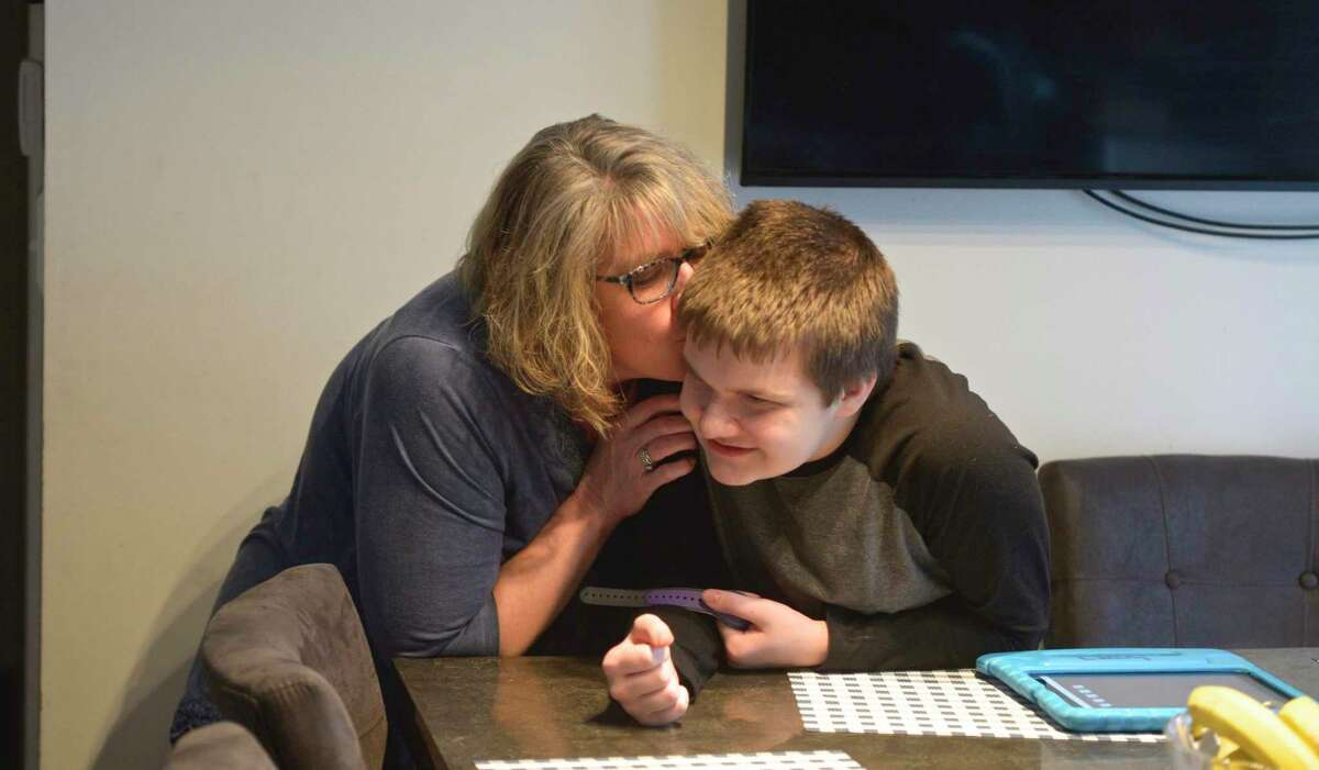 Tammy McInerney and her son Liam hang out in the family's kitchen on February 13, 2020, in New Milford, Conn., after Liam returned home after school.