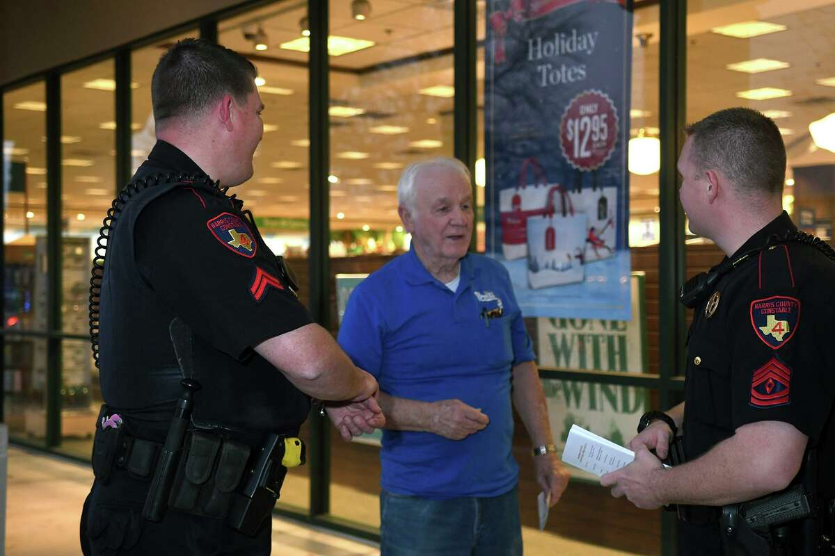 In this photo from 2017, Corporal Daniel Lynch, left, and Sgt. Aaron Strain, right, from the Harris County Pct. 4 Constable's Office, visit with Bill James who was on his way to Barnes and Nobles in Champion Forest, during the officer's patrol to promote robbery prevention and personal safety on Dec. 20, 2017. (Photo by Jerry Baker/Freelance)