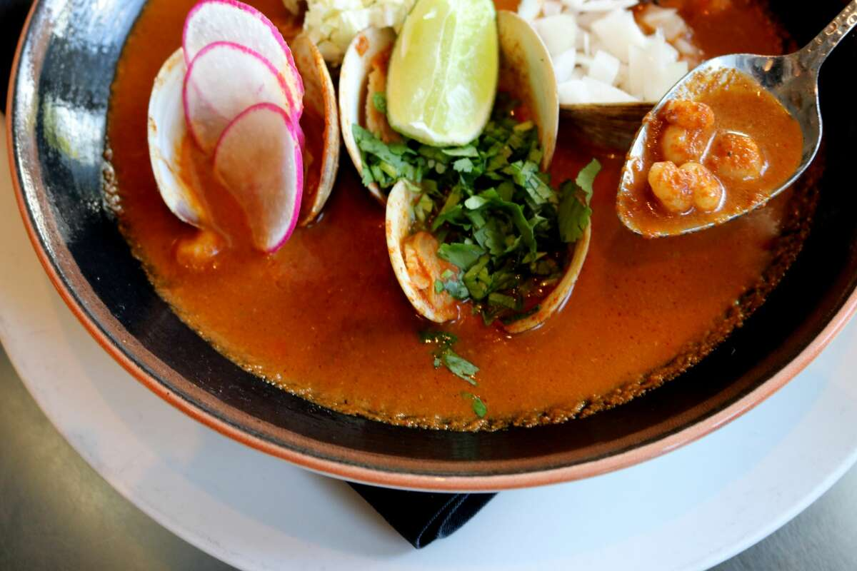 The red sauce in a pozole rojo is typically made from chiles such as guajillo, piquinor ancho. Below is the recipe for pozole rojo with clams, courtesy of Ortega. Ingredients: 4 cups cooked hominy (procedure below)1/4 cup slaked lime (calcium hydroxide)3-1/2 quarts fish or shrimp stock (or chicken stock), divided48 cooked little neck clams (procedure below) Garnishes: 1/2 cup diced onion1 cup sliced radishes2 avocados, cubed6 lime halves12 tostadas Pozole sauce: 3 dried puya peppers3 dried guajillo pepper1/2 cup pumpkin seeds1 Tbsp. sesame seeds5 black peppercorns1/4 tsp. cumin 4 whole cloves3 whole garlic cloves1 bay leaf1 cup white onion, chopped3 garlic cloves, roasted