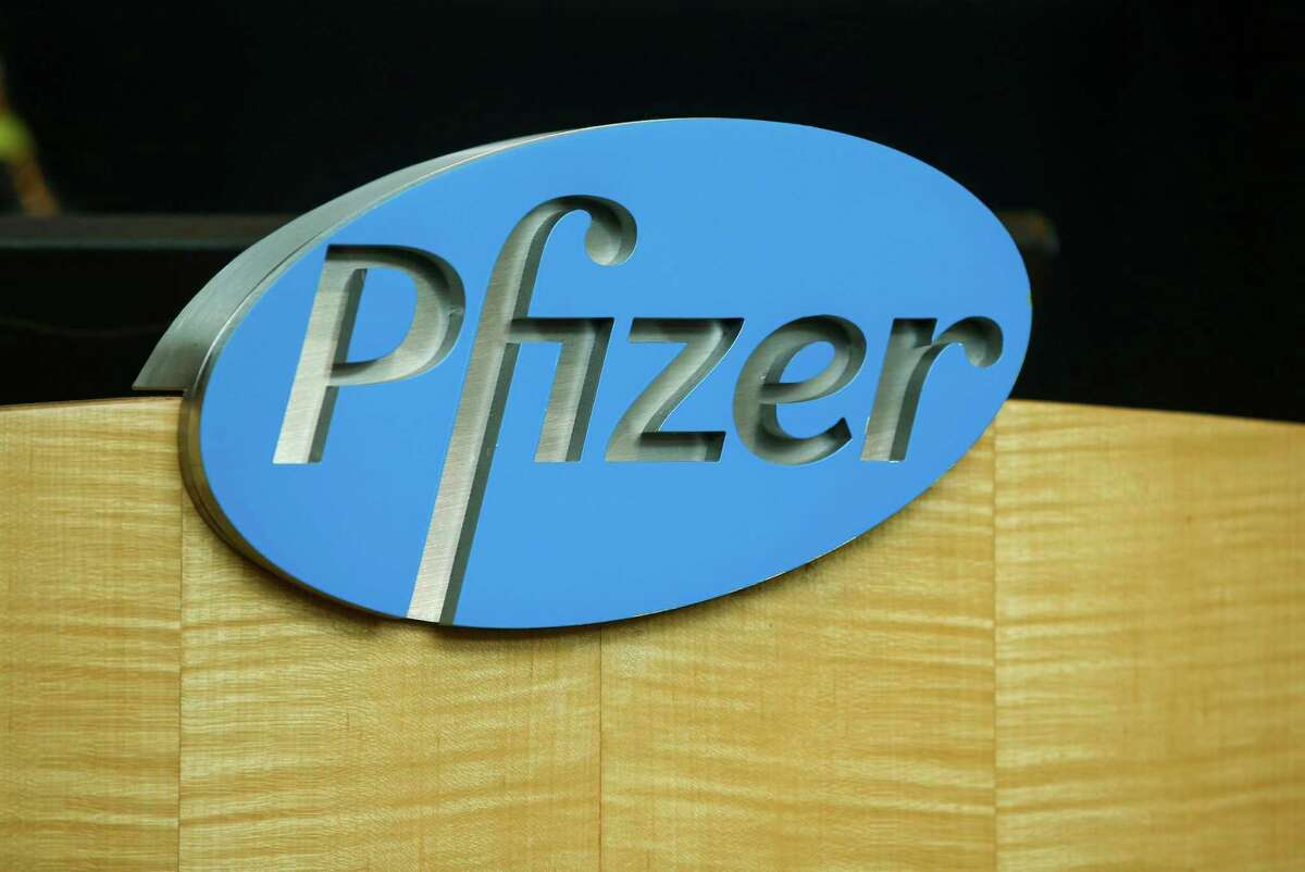 FILE - In this file photo dated Wednesday, July 22, 2020, a Pfizer sign is seen on a podium at the Pfizer Research & Development Laboratories, in Groton, USA. The U.K. health authorities rolled out a national mass vaccination program Tuesday Dec. 8, 2020, using the Pfizer-BioNTech COVID-19 vaccine. U.K. regulators said Wednesday Dec. 9, 2020, that people who have a