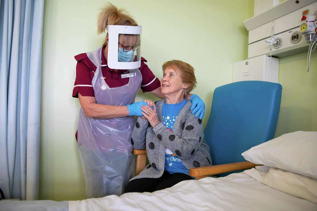 TOPSHOT - Margaret Keenan, 90, who was the first patient in the United Kingdom to receive the Pfizer-BioNtech Covid-19 vaccine, reacts as she talks with Healthcare assistant Lorraine Hill, while preparing to leave University Hospital Coventry, in Coventry on December 9, 2020, a day after receiving the vaccine. - Britain on December 8 hailed a turning point in the fight against the coronavirus pandemic, as it begins the biggest vaccination programme in the country's history with a new Covid-19 jab. (Photo by Jonny Weeks / POOL / AFP) (Photo by JONNY WEEKS/POOL/AFP via Getty Images)