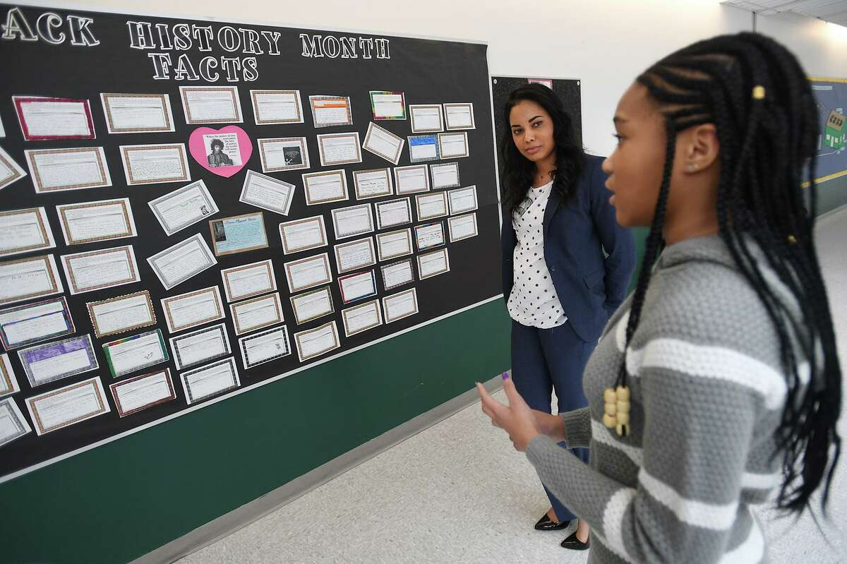 Math Specialist Tegan Willis, left, worked with seventh grader Danae Whitaker, 12, to create two Black History Month displays at Hamden Middle School in Hamden, Conn. on Wednesday, February 27, 2019.