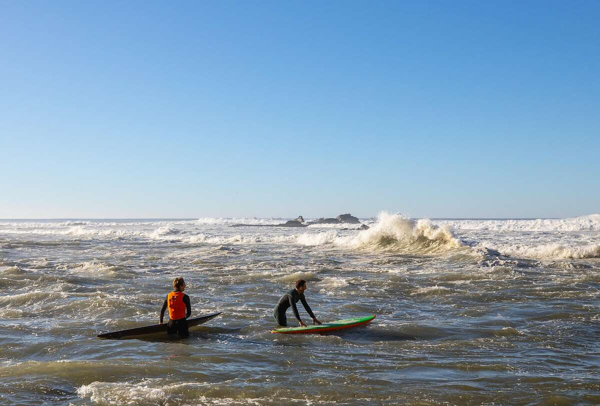 Matt Lopez, right, gets ready to paddle out at Mavericks on December 8,2020 in Halfmoon Bay, Calif.