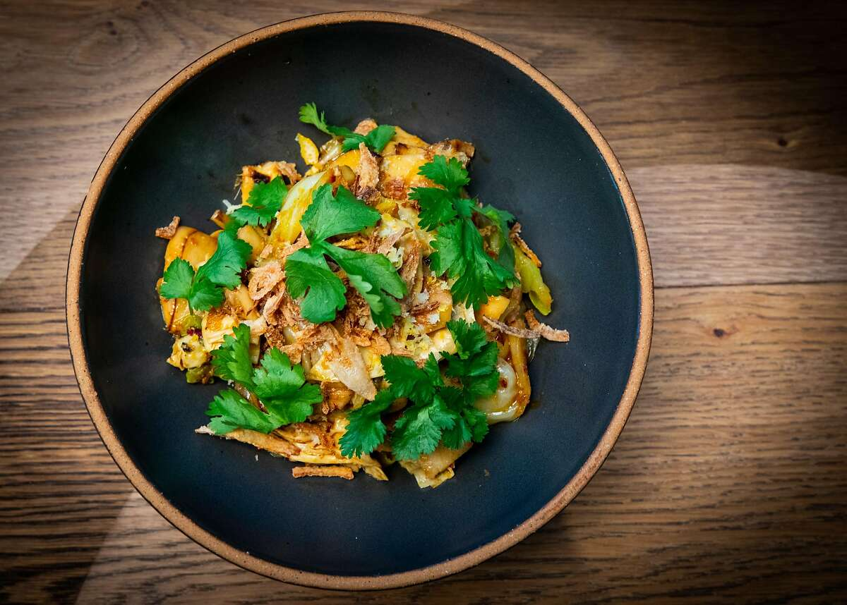 A dish of wok-charred king trumpet mushrooms, Hodo yuba and Taiwanese cabbage in lemongrass chile sauce is one of the menu items included with dinner kits at Claws of Mantis, a pop-up restaurant in S.F.