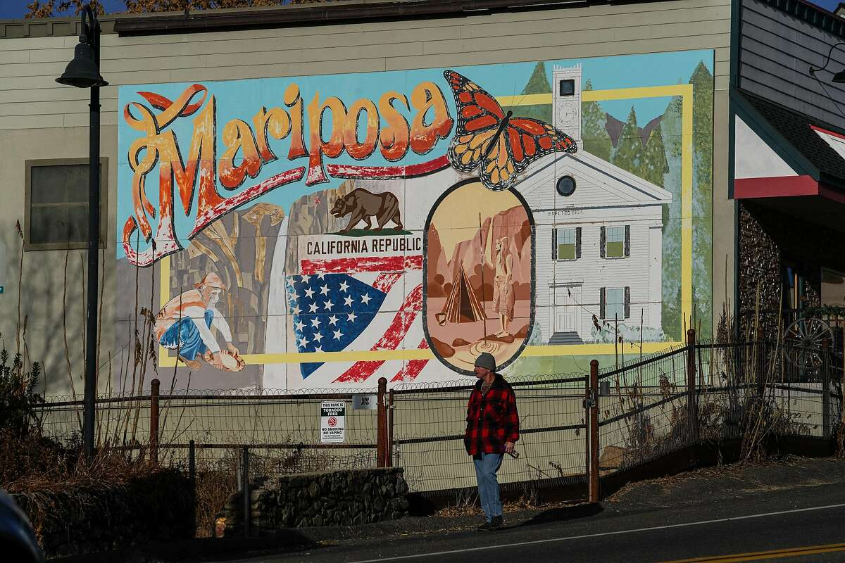 A person walks in front of a Mariposa mural along Main Street in downtown Mariposa.
