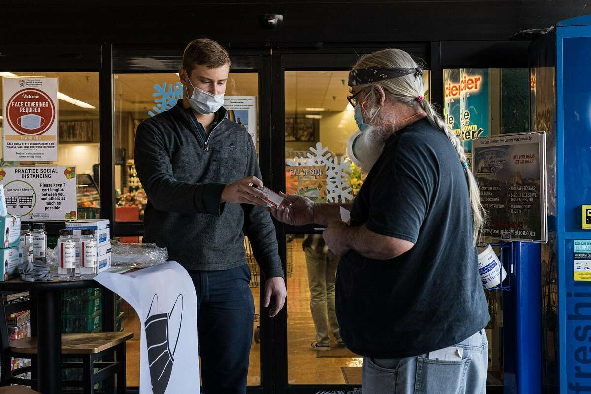 Chase Dubberke, manager of Pioneer Market, hands out sanitizer to a customer.