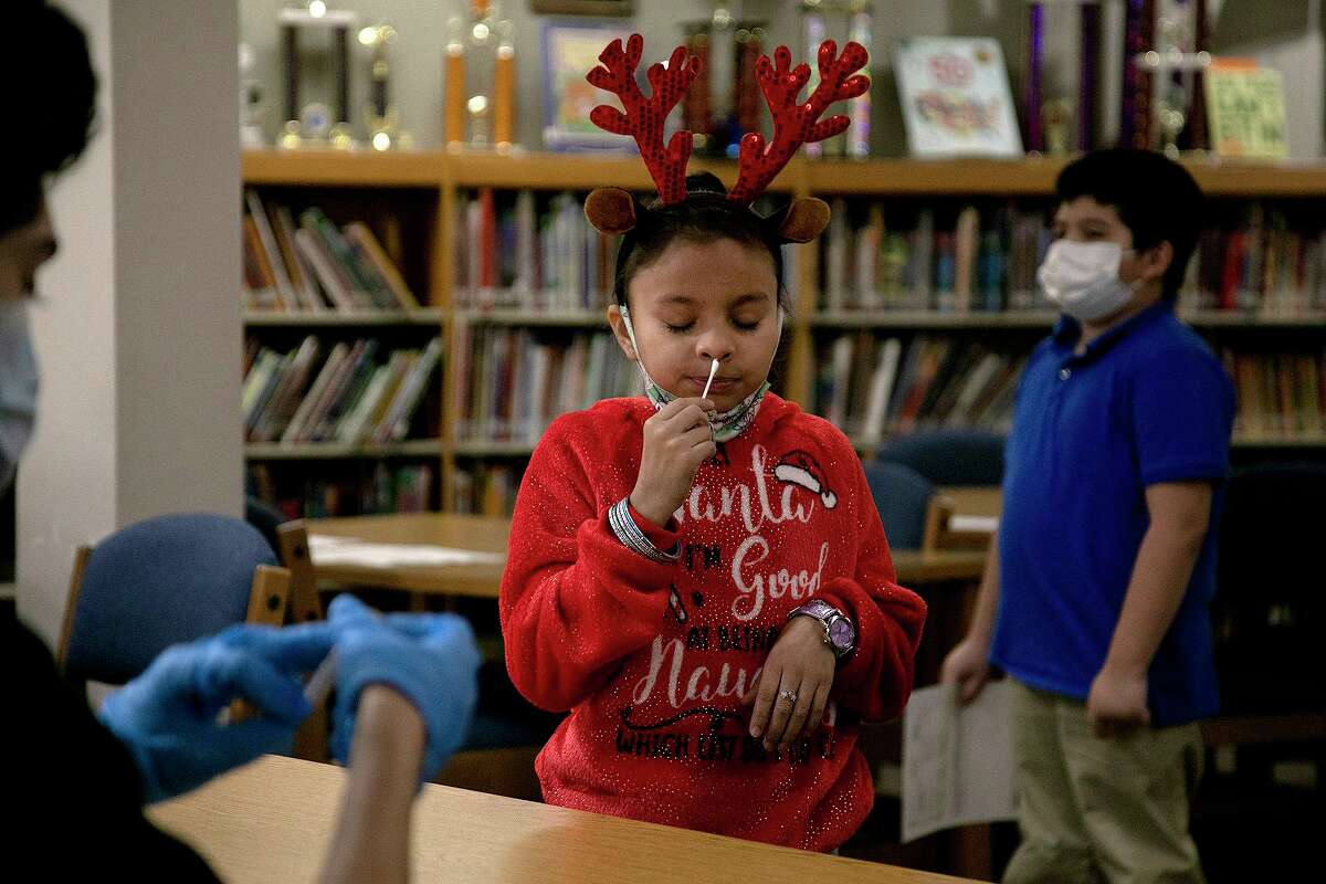 Stafford Elementary School student Brianna Avila Chavez swabs her nose for a COVID-19 test by Community Labs in the school's library on Wednesday, Dec. 9, 2020. Edgewood ISD, with Community Labs, began offering COVID-19 testing at all campuses Wednesday. High Schools in the district began testing earlier in the school year.