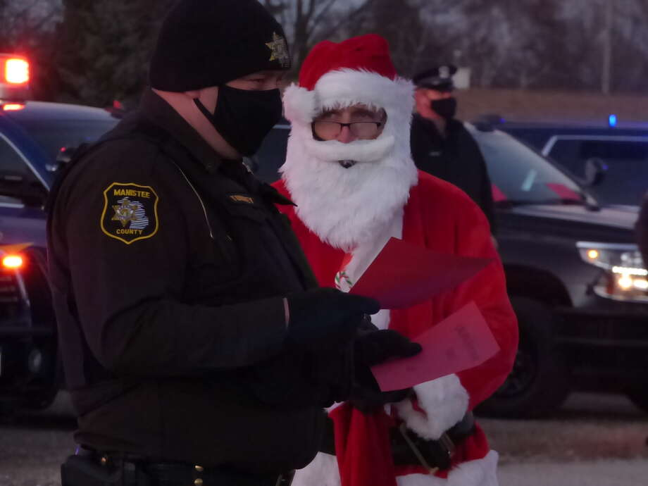 """First responders from eight different organizations in Manistee County took part in the annual Shop with a Hometown Hero event on Wednesday, which took on a new look due to the pandemic. Instead of shopping, the """"heroes"""" delivered gifts to families in the parking lot of Manistee Catholic Central. Photo: Scott Fraley/News Advocate"""