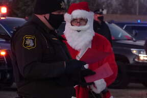 """First responders from eight different organizations in Manistee County took part in the annual Shop with a Hometown Hero event on Wednesday, which took on a new look due to the pandemic. Instead of shopping, the """"heroes"""" delivered gifts to families in the parking lot of Manistee Catholic Central."""