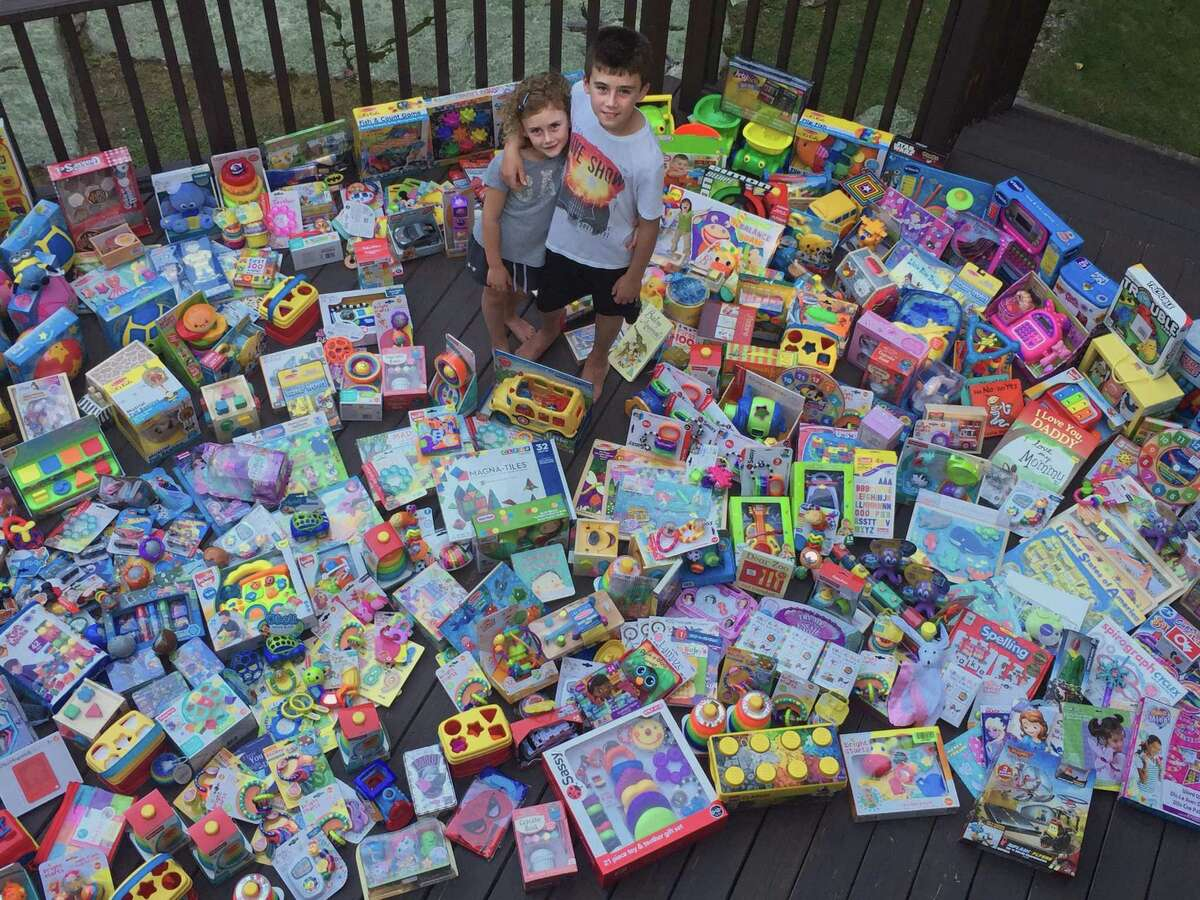 Owen and Emmy Bernheim with some of the 701 toys they collected from a 2016 pre-pandemic toy drives and birthday parties.