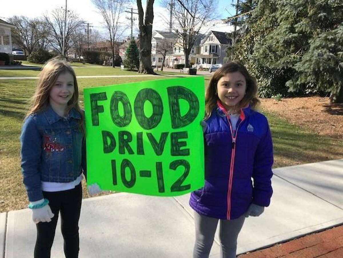 Two people hold a sign for a food drive that is going to be held on Saturday, Dec. 12 at Berskhire Hathaway, 1583 Post Road, Fairfield Center, in Fairfield.