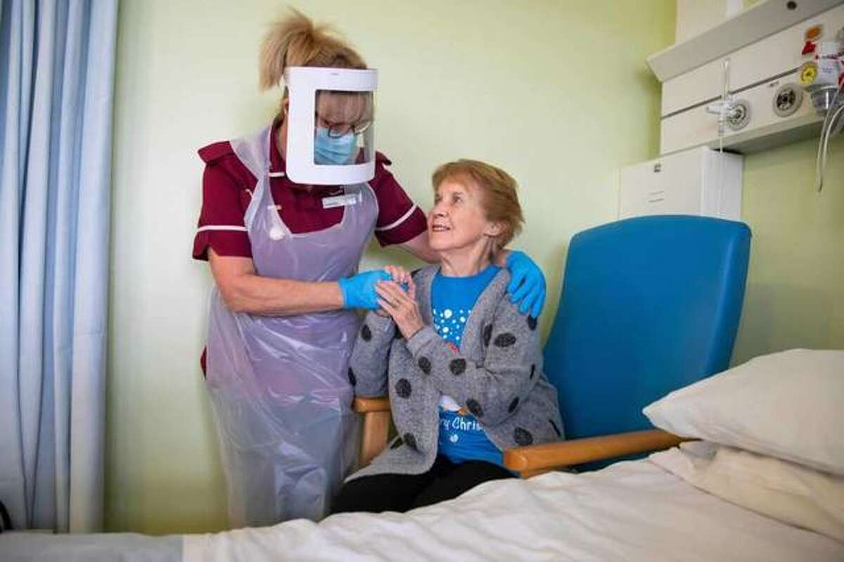 Margaret Keenan, 90, who was the first patient in the United Kingdom to receive the Pfizer-BioNtech COVID-19 vaccine, reacts as she talks with healthcare assistant Lorraine Hill, while preparing to leave University Hospital Coventry, in Coventry, in central England, on Dec. 9, 2020, one day after receiving the vaccine.