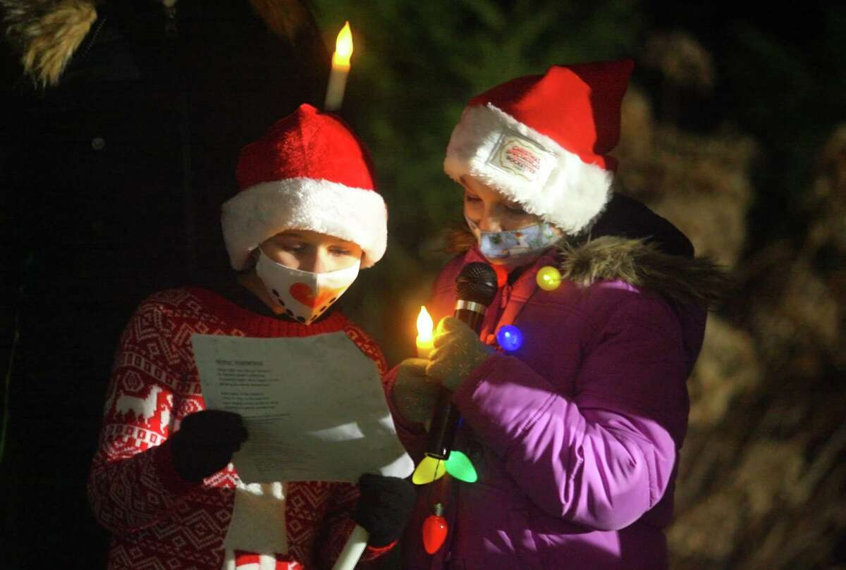 Carolers Megan Panepento and her sister Jenna perform outside for senior residents at Maplewood at Stony Hill, in Bethel, Conn., on Wednesday Dec. 8, 2020. Newtown Youth and Family Services organized the event.