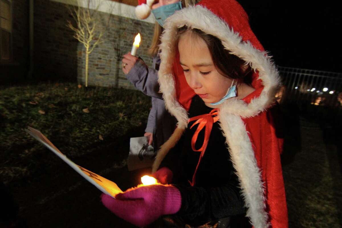 Bailey Moran, 7, joins with other children from Newtown Youth and Family Services to sing Christmas carols for senior residents at Maplewood at Stony Hill, in Bethel, Conn., on Wednesday Dec. 8, 2020.