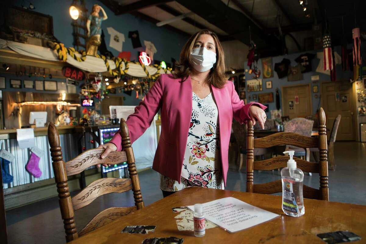 Kelly Railean, master distiller and co-founder at Railean Distillers, stands at a table with hand sanitizer and a sign limiting only 6 people to a table in the bar Wednesday, Dec. 9, 2020 in San Leon. The distillery and its associated bar has had to cut way back on its business operations due to Covid-19 restrictions.