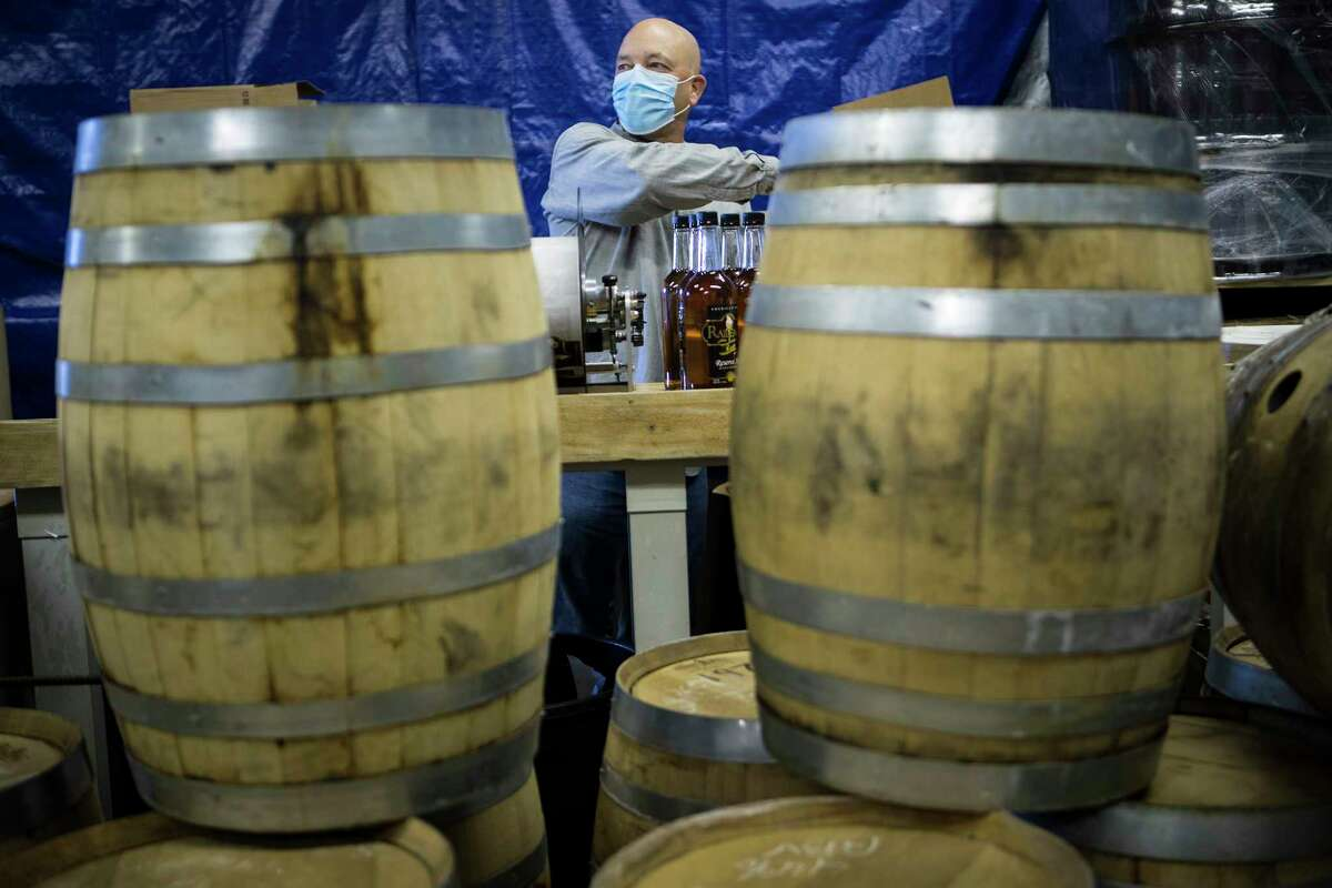 Kenny Bradshaw, master distiller and Vice President of operations at Railean Distillers, caps rum bottles Wednesday, Dec. 9, 2020 in San Leon. The distillery and its associated bar has had to cut way back on its business operations due to Covid-19 restrictions.