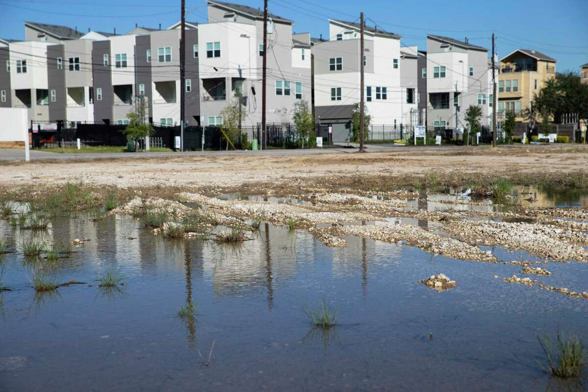A puddle sitting on an empty field at Clinton and Jensen Drives that is waiting to be developed Wednesday, Dec. 9, 2020, at Fifth Ward in Houston. A city agency supports a huge development proposed along south of Clinton Drive between Jensen Drive and Hirsch Road. Community activists worry the development will drive out existing low-income residents in the historical Black neighborhood.