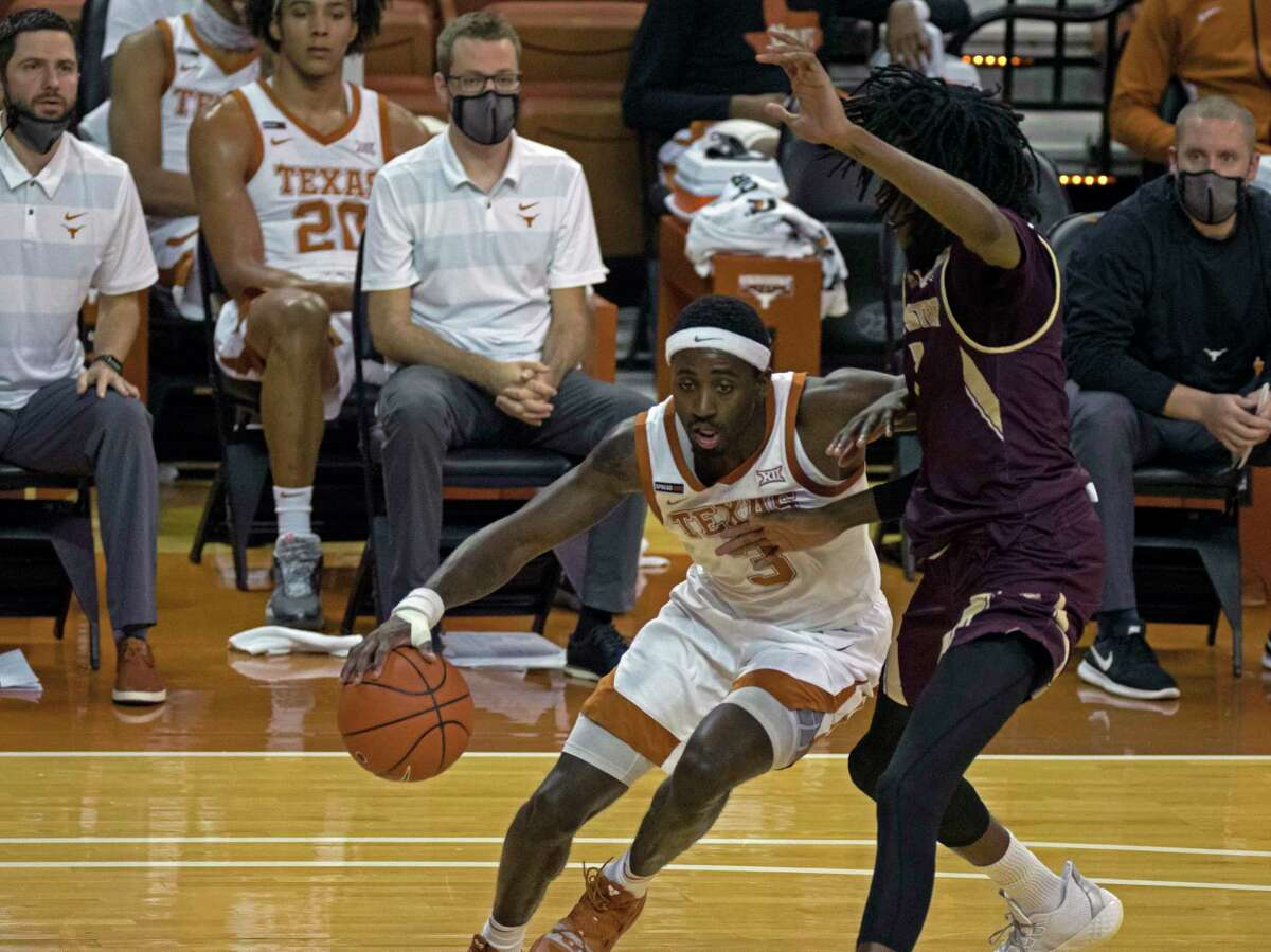 Texas guard Courtney Ramey (3) drives around Texas State guard Isaiah Small during the second half of an NCAA college basketball game, Wednesday, Dec. 9, 2020, in Austin, Texas. (AP Photo/Michael Thomas)
