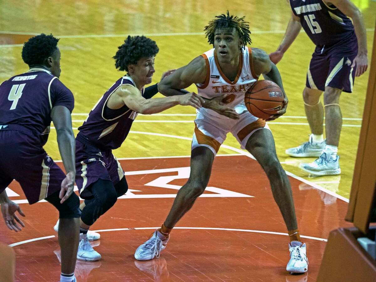 Texas forward Greg Brown, right, looks to shoot against Texas State guard Mason Harrell, left, during the second half of an NCAA college basketball game, Wednesday, Dec. 9, 2020, in Austin, Texas. Texas won 74-53. (AP Photo/Michael Thomas)