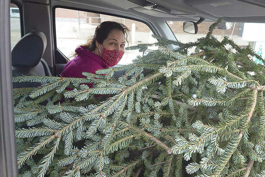 Marisa Burly drives away after buying one of the last trees available at a Christmas tree lot in Chicago. Sales of Christmas trees have been up as people around the country are looking for ways to lift their spirits during the coronavirus pandemic. Photo: Scott Olson | Getty Images