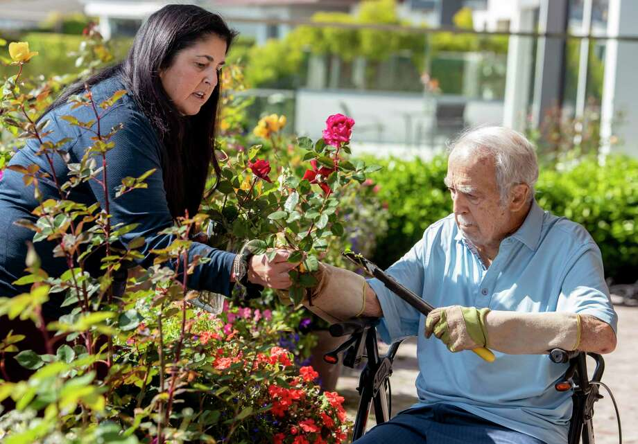 Mary Amen, left, helps her father, Louis Amen, 90, cut roseslast spring at his home in Newport Beach, California. (Photo by Leonard Ortiz/MediaNews Group/Orange County Register via Getty Images) / Orange County Register/SCNG
