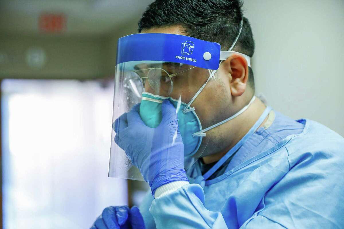 Nurse Nestor Cardenas tightens his mask before going into a room with a COVID-19 patient at Regional Medical Center of San Jose, an acute-care hospital, on Tuesday, Dec. 8, 2020 in San Jose, California.