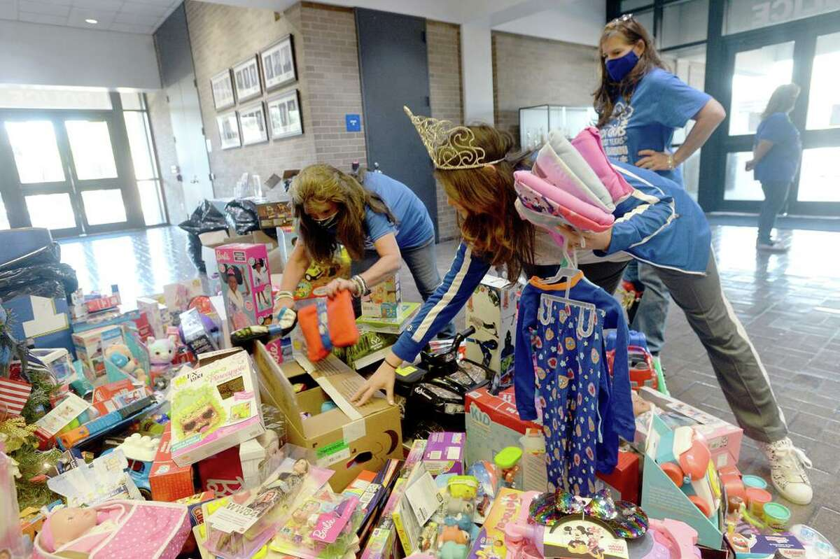 Mardi Gras of Southeast Texas members, including Jeanine Hebert (left), Jerri McCown and Carrie Queen Garcia, set out the boxes and bags of toys collected in their 9th annual Krewe of Krewes