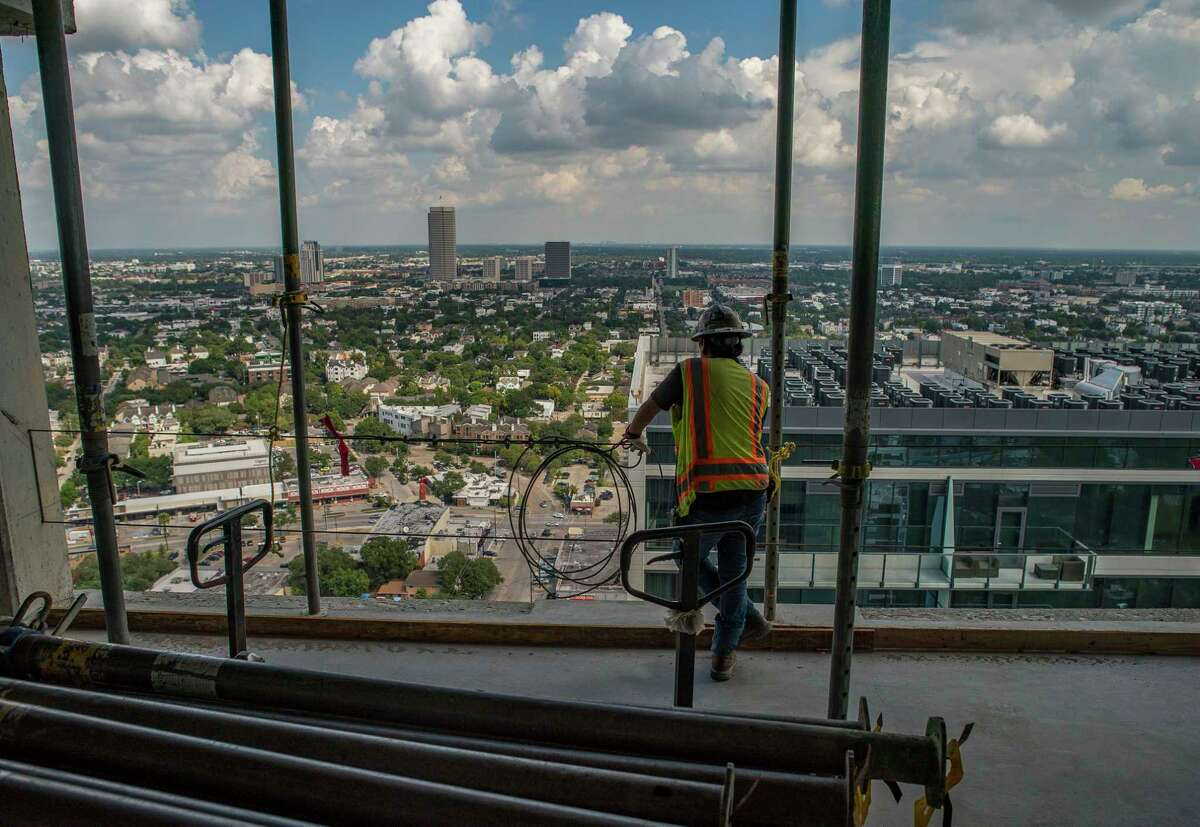 A construction worker looks at the view during a visit to the 33rd floor of the La Colombe d'Or Hotel & Residences to mark the topping out of the building in Houston's Montrose neighborhood, Tuesday, Sept. 10, 2019. The Developer Hines is building the 265-unit, high-rise luxury multifamily project next to the historic La Colombe d'Or Hotel.