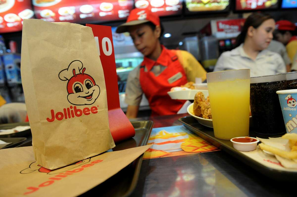 Philippines' leading fast-food giant Jollibee Foods employees attend to customer orders at a Jollibee store in Manila on October 14, 2015. (JAY DIRECTO/AFP via Getty Images)