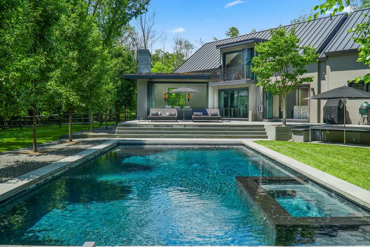 """A heated swimming pool and spa at 42 Meeker Hill Road in Redding. Only a mélange of MOMA and an Audubon Society sanctuary would be suitable for this 4,009-square-foot gray house custom-built in 2017, combining uncluttered minimalism with the property's lush landscape. It was designed for visual enjoyment throughout the four seasons. """"This is one of the (most) beautifully designed homes I have ever represented. Upon entering you feel surrounded by a sense of calm and serenity. This Zen-like environment embraces the natural beauty of the outdoors and brings it in,"""" said Denise Gannalo, the listing agent."""