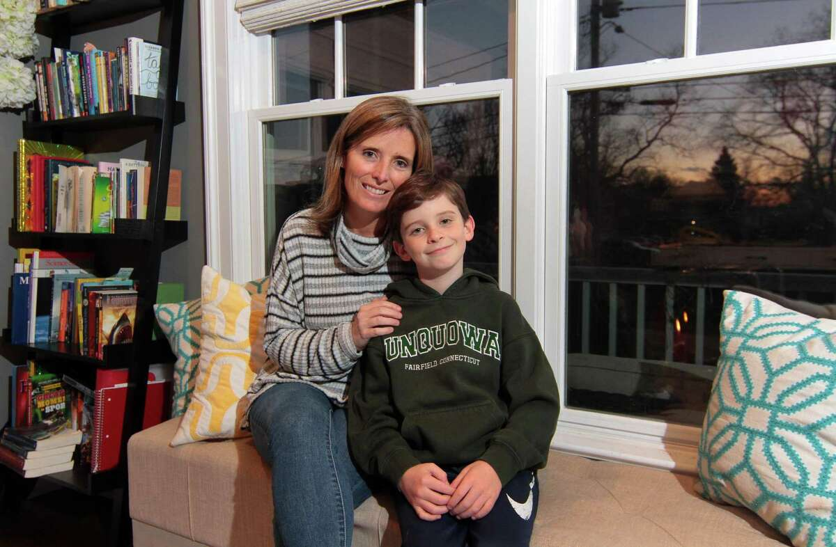Crissy Kelly poses with her son James, 9, at their home in Fairfield, Conn., on Tuesday Dec. 8, 2020. son James, a student at Unquowa School, attends classes in person.