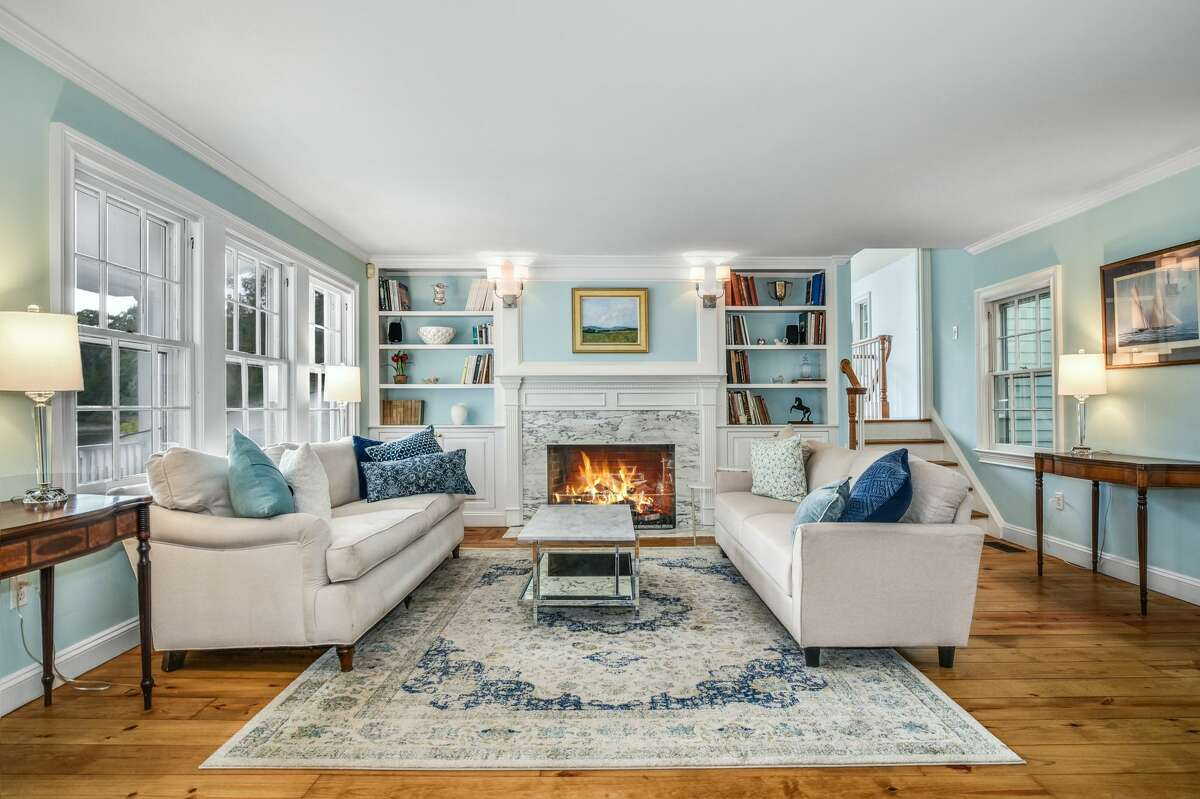 A family room with marble fireplace at 71 Goodwives River Road in Darien. The south and west facing property allows the home's residents to enjoy sunsets.