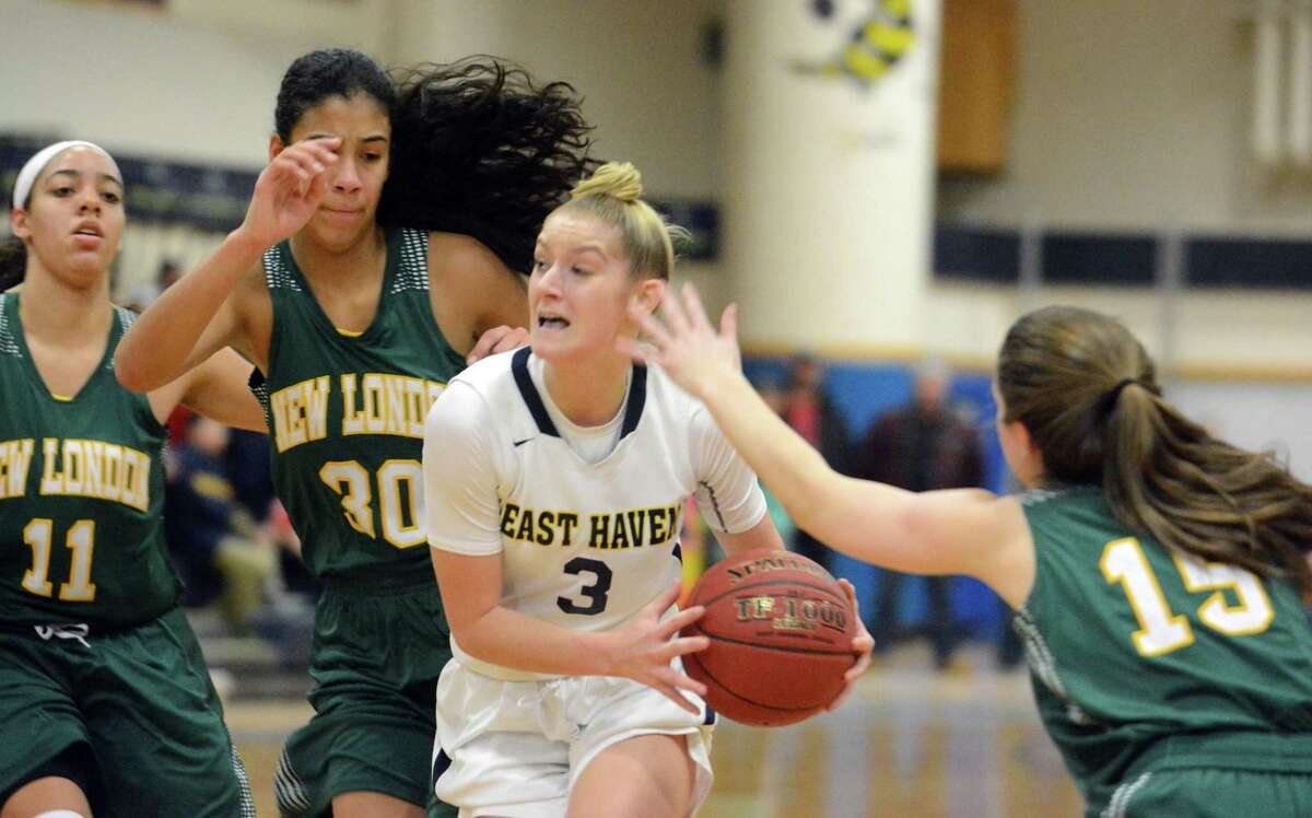East Haven's Makenzie Helms splits the defense of New London's Taina Pagan (30) and Angelina Munoz (15) in 2018.