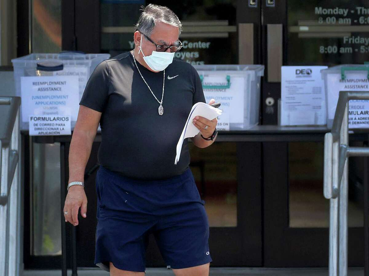 Ricardo Duque recently lost his restaurant job due to the coronavirus outbreak. He looks over an unemployment application he picked up at the CareerSource Broward office on Oakland Park Boulevard on April 9, 2020. (Mike Stocker/Sun Sentinel/TNS)