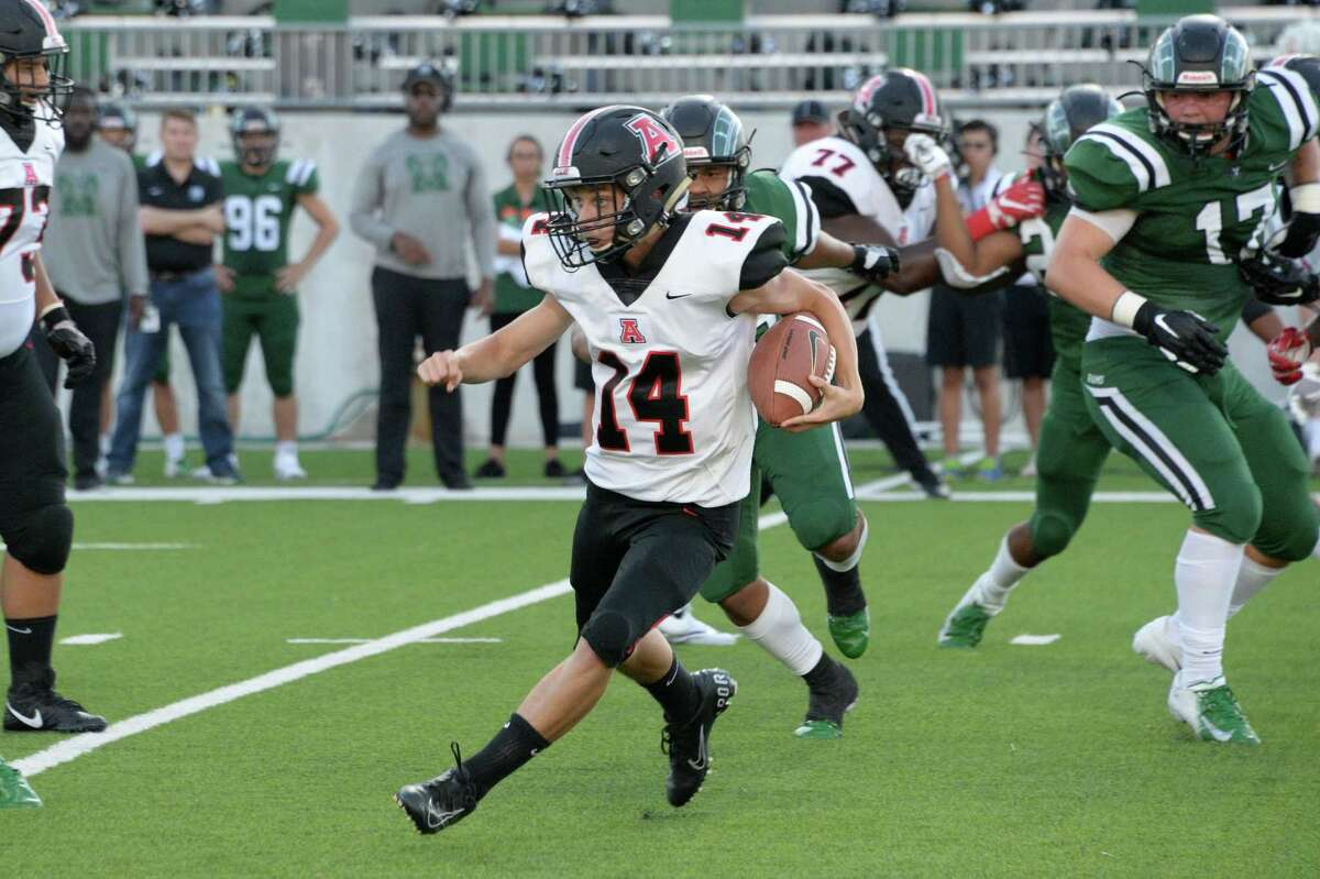 Braeden Abboud (14) of Ft. Bend Austin carries the ball on a quarterback keeper in the second quarter of a non-district football game between the Mayde Creek Rams and the Ft. Bend Austin Bulldogs on Saturday, September 7, 2019 at Legacy Stadium, Katy, TX.