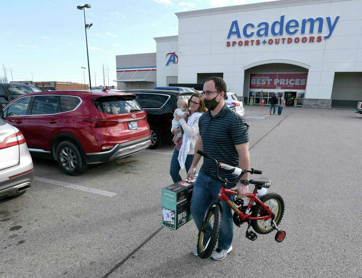 Aaron and Jessica Elder, of Hartford, carrying Boyd, 7 months, purchased two bikes for their children for Christmas presents while shopping on Black Friday at Academy Sports + Outdoors in Owensboro, Ky., Friday, Nov. 27, 2020. (Alan Warren/The Messenger-Inquirer via AP)