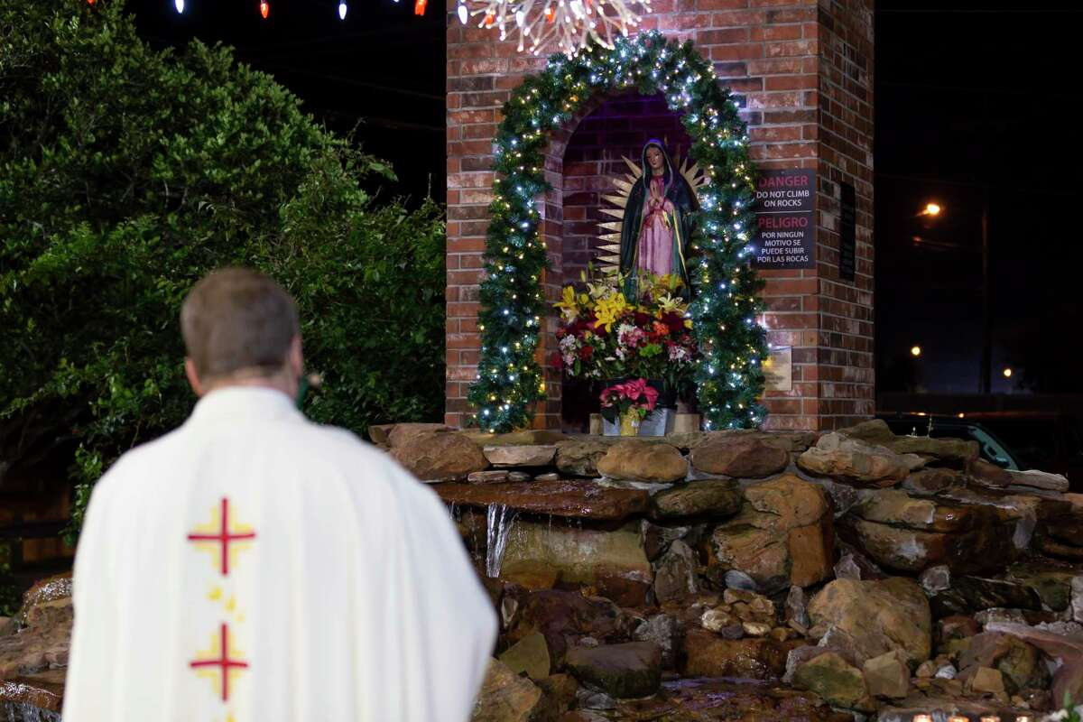 Rev. Phillip Wilhite leads a rosary service while wearing a custom Virgin of Guadalupe mask at the grotto near Sacred Heart Catholic Church.