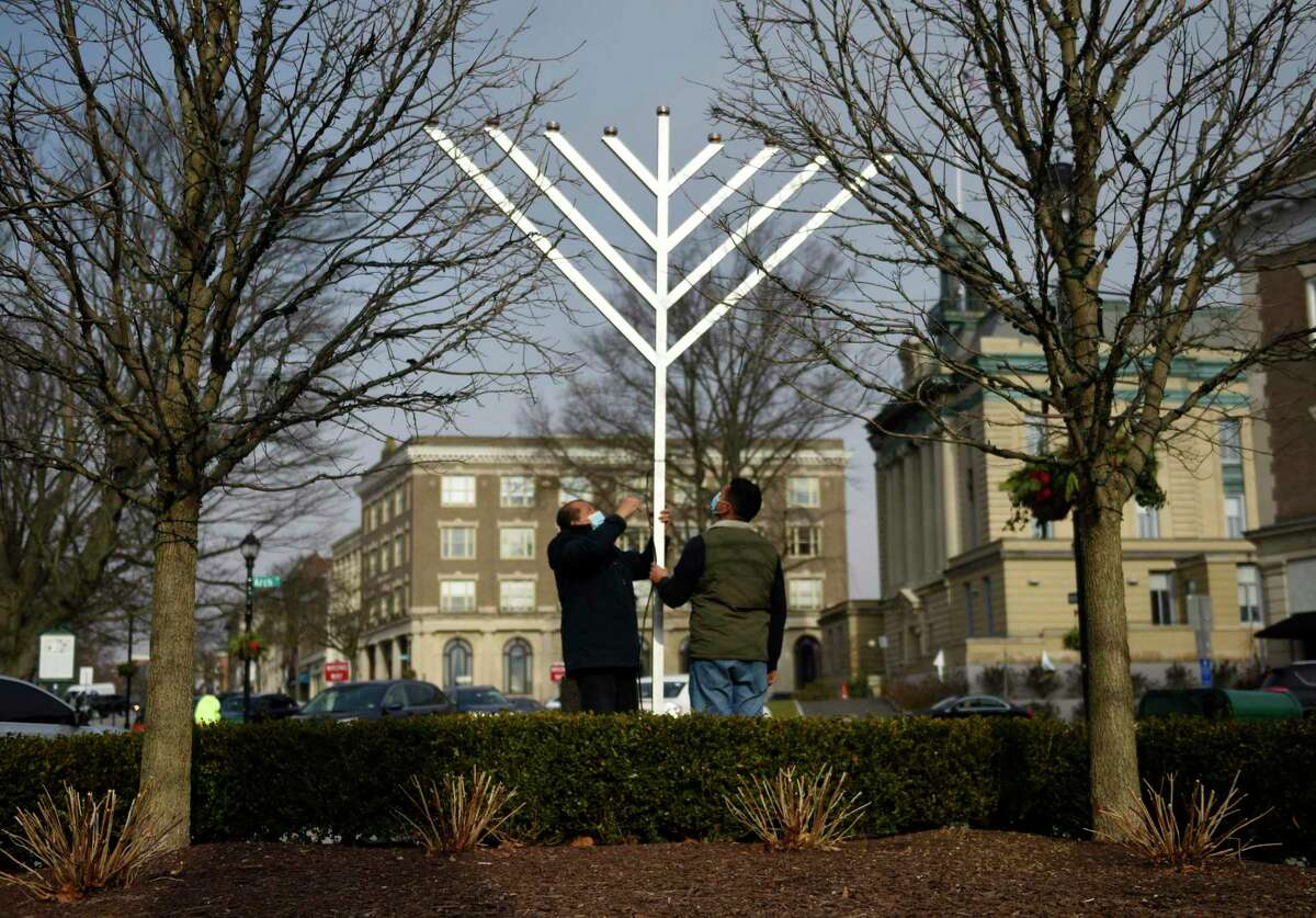Bernard Garcia, left, and Edras Sand install a giant menorah from Chabad Lubavitch of Greenwich at the intersection of Greenwich Avenue and Arch Street in Greenwich on Dec. 9. Hanukkah started Dec. 10 and lasts through Dec. 18.