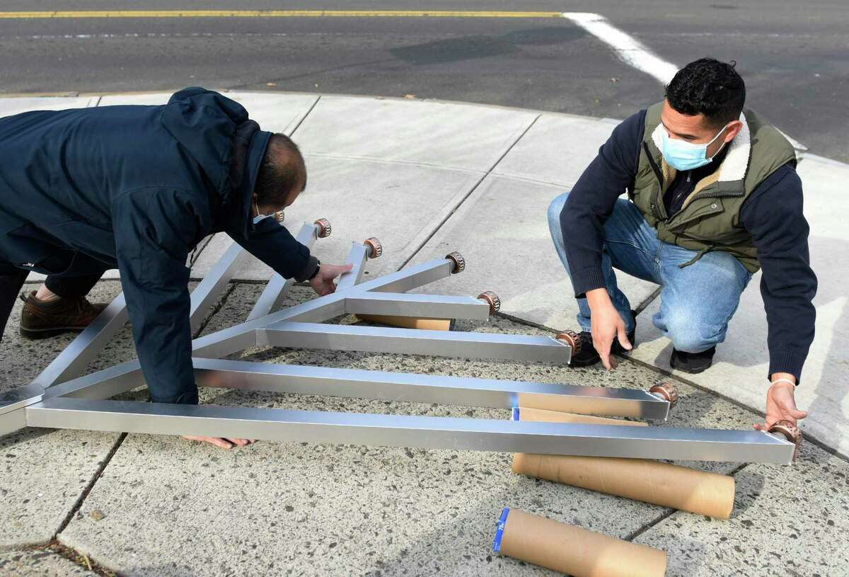 Bernard Garcia, left, and Edras Sand install a giant menorah from Chabad Lubavitch of Greenwich at the intersection of Greenwich Avenue and Arch Street in Greenwich, Conn. Wednesday, Dec. 9, 2020. Hanukkah starts the evening of Thursday, Dec. 10 and lasts through Dec. 18.