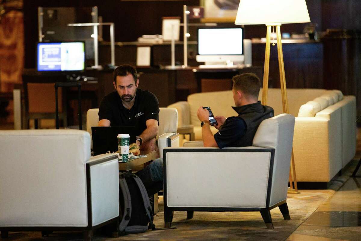 Hilton Americas-Houston guests have coffee on the hotel lobby, Wednesday, Nov. 11, 2020, in Houston.