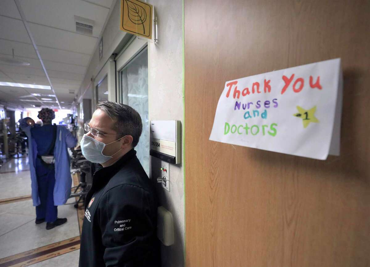 A thank you note for staff at UW Health is displayed on a wall inside a COVID-19 treatment unit as Dr. Andrew Braun, a physician on the unit, stands by in Madison, Wis. last month. Medical teams from U.S. Army North, including units from Fort Sam Houston in San Antonio, are headed for Wisconsin to support hospitals grappling with the pandemic.