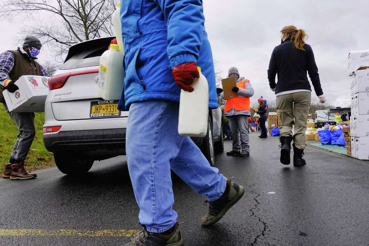 Volunteers load food into vehicles during a mass food distribution put on by Catholic Charities of the Diocese of Albany, and the Regional Food Bank of Northeastern New York on Thursday, Dec. 10, 2020, in Schenectady, N.Y. The next mass food distributions will be on Monday Dec. 14th, at Metropolitan Church, located at 105 2nd St, in Albany, and then on Wednesday, Dec. 16th, at SUNY Schenectady college. Both events begin at 9:30AM. The distribution is open to the public and no pre-registration is required. Food is distributed on a first-come, first-served basis, and the distribution will last until supplies are gone. (Paul Buckowski/Times Union)
