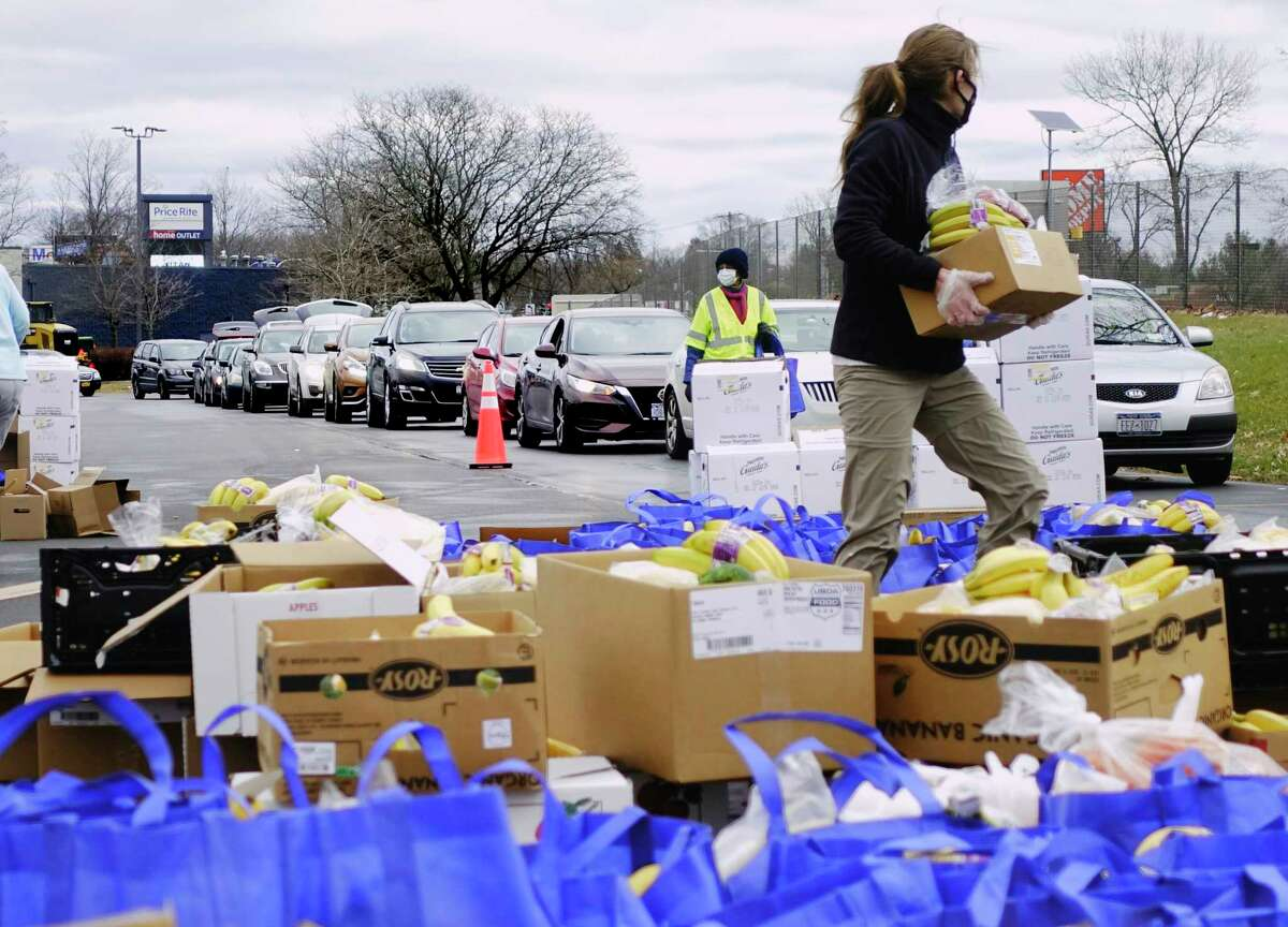 Drivers in their cars are lined up as they wait their turn as volunteers load food into vehicles during a mass food distribution put on by Catholic Charities of the Diocese of Albany, and the Regional Food Bank of Northeastern New York on Thursday, Dec. 10, 2020, in Schenectady, N.Y. The next mass food distributions will be on Monday Dec. 14th, at Metropolitan Church, located at 105 2nd St, in Albany, and then on Wednesday, Dec. 16th, at SUNY Schenectady college. Both events begin at 9:30AM. The distribution is open to the public and no pre-registration is required. Food is distributed on a first-come, first-served basis, and the distribution will last until supplies are gone. (Paul Buckowski/Times Union)