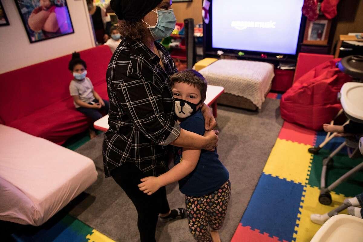 Fouziya Bawazir hugs Ireland Broussard-Rain, 5, one of the children she cares for, at Wishing Well Daycare in Hayward.