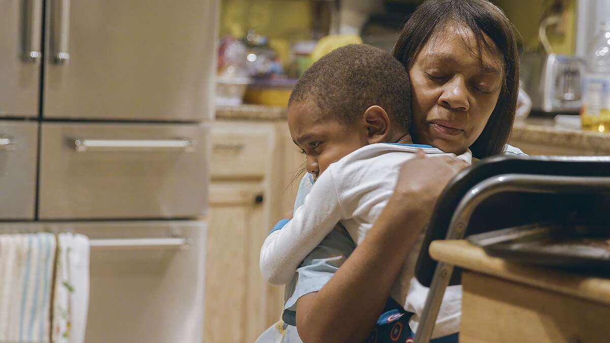 """Deloris Hogan comforts one of her child care children in the documentary """"Through the Night."""""""