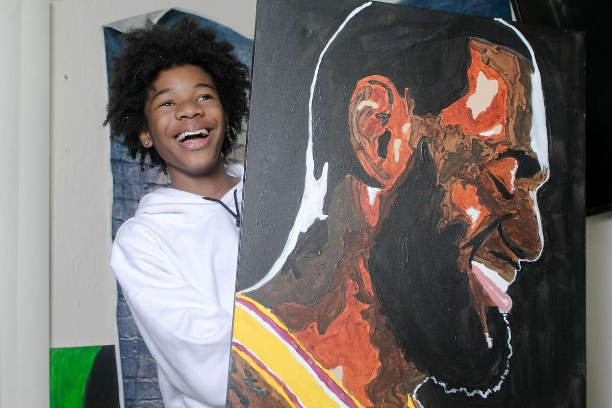 Tyler Gordon, a 14-year-old artist, poses with his artwork at his home in San Jose, Calif., on Dec. 7, 2020. Tyler's portraits have gone viral recently, so much so that he has received a phone call from Kamala Harris, after she saw his work. He also painted the recent cover of LeBron James for Time magazine.