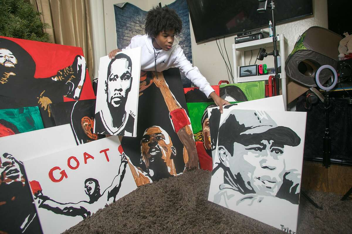 Tyler Gordon, a 14-year-old artist, poses with his artwork at his home in San Jose, Calif., on Dec. 7, 2020. Tyler's portraits have gone viral recently, so much so that he has received a phone call from Kamala Harris, after she saw his work. He also drew the recent cover of LeBron James for Time magazine.