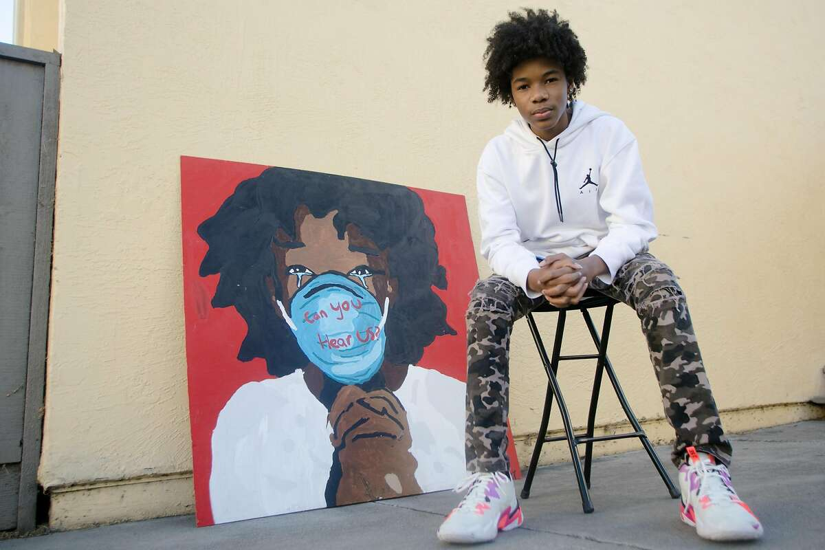 Tyler Gordon, a 14-year-old artist, poses in front of his artwork at his home in San Jose, Calif., on Dec. 7, 2020. Tyler's portraits have gone viral recently, so much so that he has received a phone call from Kamala Harris, after she saw his work. He also painted the recent cover of LeBron James for Time magazine.