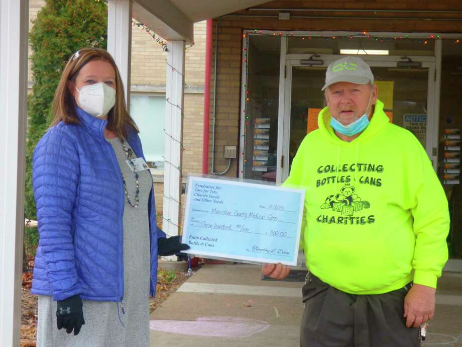 Tonja Robles accepts a $300 check on behalf of the Manistee County Medical Care Facility from Kaleva-resident Tim Dean. (Courtesy Photo)